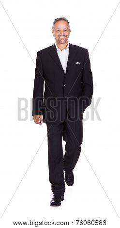 Smiling mature businessman walking