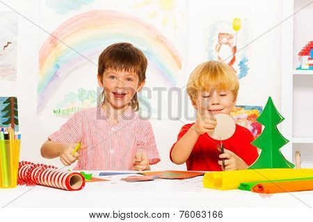 Happy boys make Xmas decorations with scissors