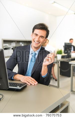 Man at his office desk holding a business card