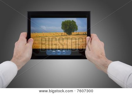 Male Hand Holding A Touchpad Pc Showing A Movie