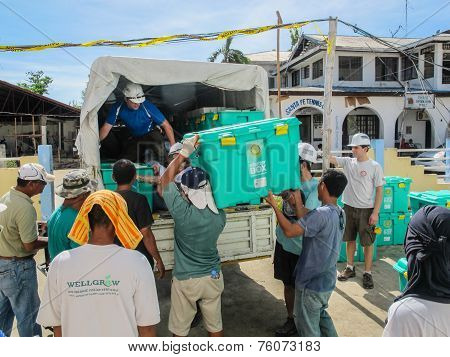 UK overseas aid workers loading ShelterBox emergency aid onto trucks after Typhoon Haiyan