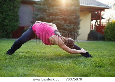 Flexible Woman Doing Exercises Outdoor In Sunset