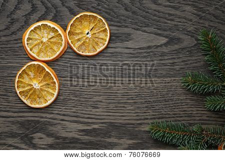 Dried Orange Slices And Spruce Twig On Dark Oak Table