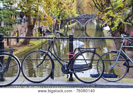Bicycle Tied To The Fence Of The Bridge Across The Canal In Utrecht