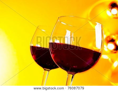 Two Red Wine Glasses Against Golden Lights Background