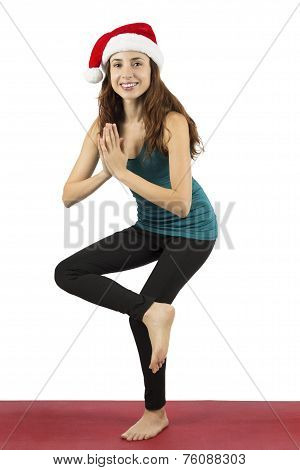 Woman With Santa Claus Hat In Tree Pose During Yoga