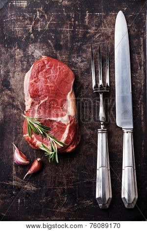Raw Fresh Meat Ribeye Steak, Rosemary And Vintage Fork And Knife Carving Set On Dark Background