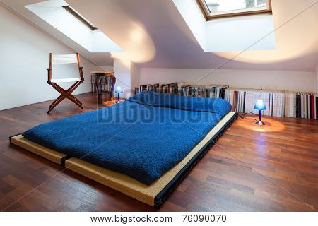 Interior, nice loft, bed with bedspread blue