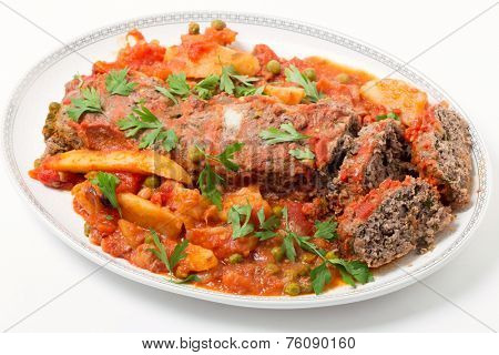 Homemade meatloaf baked in tomato sauce with peas and potatoes.