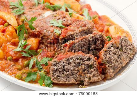 Homemade meatloaf baked in tomato sauce with peas and potatoes on a dish