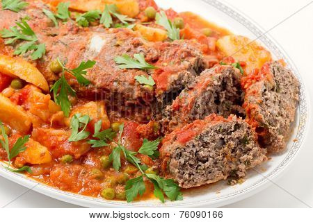 Homemade meatloaf baked in tomato sauce with peas and potatoes on a serving dish