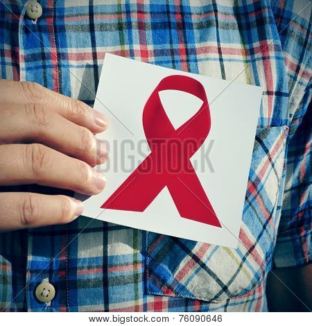 a young man holding a picture of a red ribbon, for the fight against AIDS, on his chest