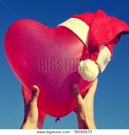 someone holding a heart-shaped balloon with a santa hat