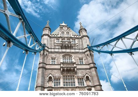 Detail of one of the towers on Tower Bridge, London with a portion of the suspension cables against a cloudy blue sky