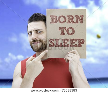 Man holding a card with the text Born to Sleep on a beach background
