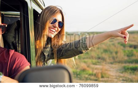 Portrait Of Beautiful Girl On Car Roadtrip Pointing Forward.