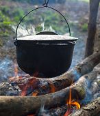 stock photo of cauldron  - Cooking in the cauldron on the open fire - JPG