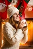 stock photo of vapor  - Smiling brunette woman in woolen sweater holding vaporing cup at fireplace