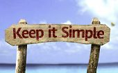 picture of understanding  - Keep It Simple sign with a beach on background - JPG