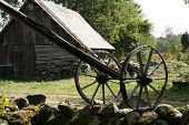 stock photo of shadoof  - Sweep well swipe with wheels and old barn on the background - JPG