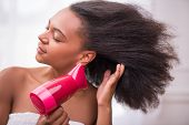image of dark-skin  - Beautiful  dark skinned girl blowing  dry her  hair with rose hairdryer  isolated on white background closing eyes - JPG