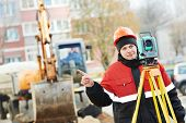 picture of theodolite  - surveyor worker working with theodolite transit equipment at road construction site outdoors - JPG