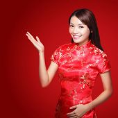image of traditional attire  - Smile Chinese woman dress traditional cheongsam and introduce on red background - JPG