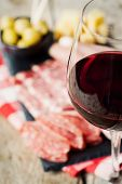 pic of charcuterie  - Glass of red wine with charcuterie assortment on the background