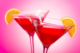 picture of vodka  - Two delicious cosmopolitan cocktails with cranberry juice vodka triple sec and fresh squeezed lime juice with an orange garnish - JPG
