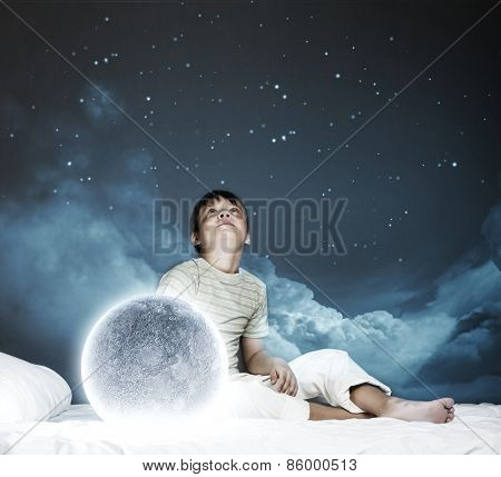 Cute boy sitting in bed with moon