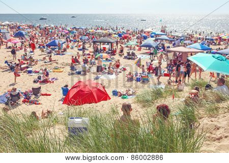 Beach scene on a busy summer day with blurred out people