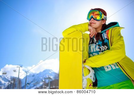 snowboarder girl standing hold snowboard against blue sky