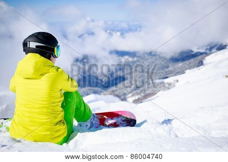 Snowboarder sitting with mountain chain in the background