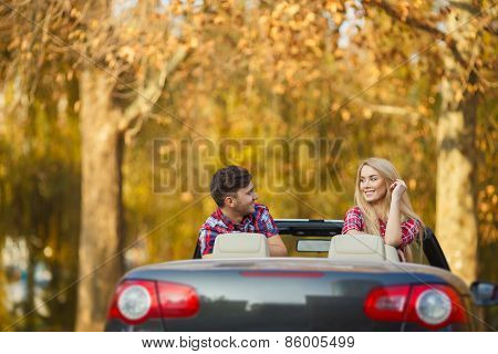 Couple in love sitting in a black convertible in the autumn Park.
