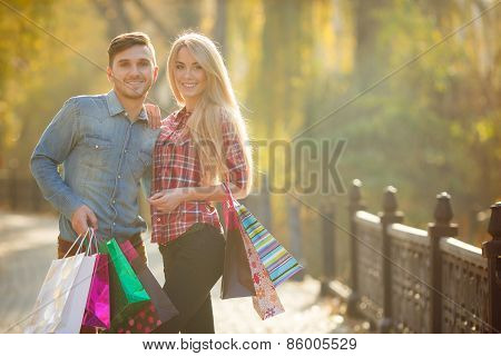 Happy young couple with a paper bag in a Park in autumn.