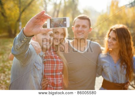 Friends are photographed with a smartphone in the Park.