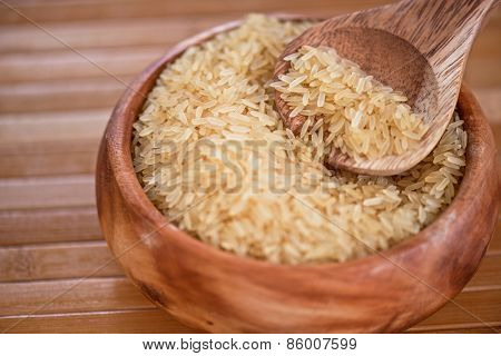 golden rice on wooden plate on wooden background