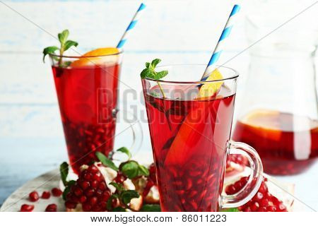 Pomegranate drink in glasses with mint and slices of orange on color wooden planks background