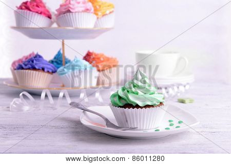 Delicious cupcakes on plate on table close-up