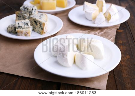 Plates of various types of cheese on sheet of paper on wooden table background
