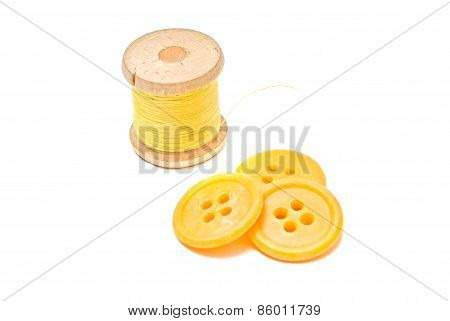 Spool Of Yellow Thread And Plastic Buttons