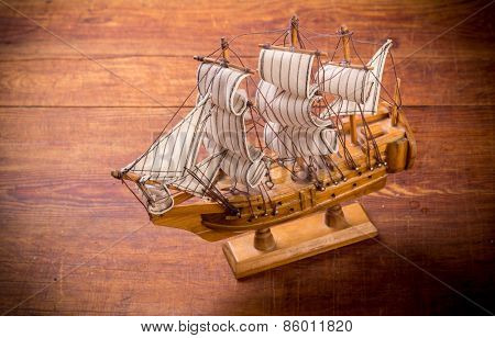 Toy sailboat on a wooden background with copy space