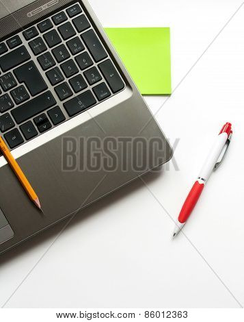 Laptop, Pencil And Pen On White Background