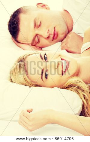 Young adult couple sleeping on the bed in bedroom
