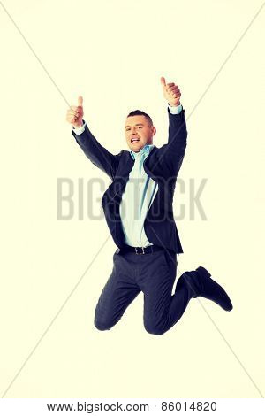 Happy businessman jumping in the air with thumbs up