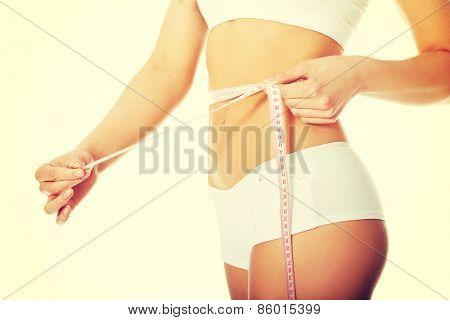 Woman measuring perfect shape of beautiful body.