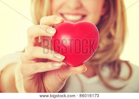 Smiling woman with red heart in hand