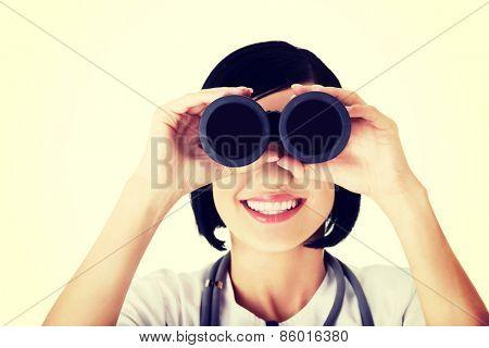 Looking in the futere of health care. Female doctor or nurse looking through binoculars.