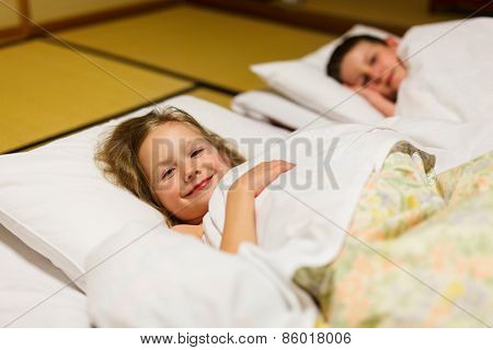 Kids sleeping on futons at traditional Japanese style room