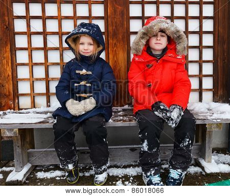 Adorable little girl and cute boy outdoors on beautiful winter day